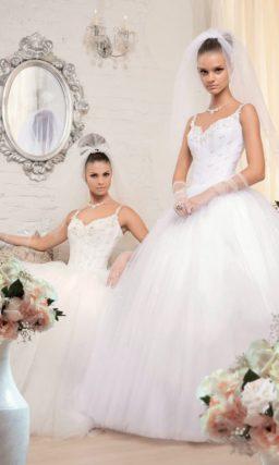 Пышное свадебное платье с вышивкой на корсете и фигурными бретельками на плечах.