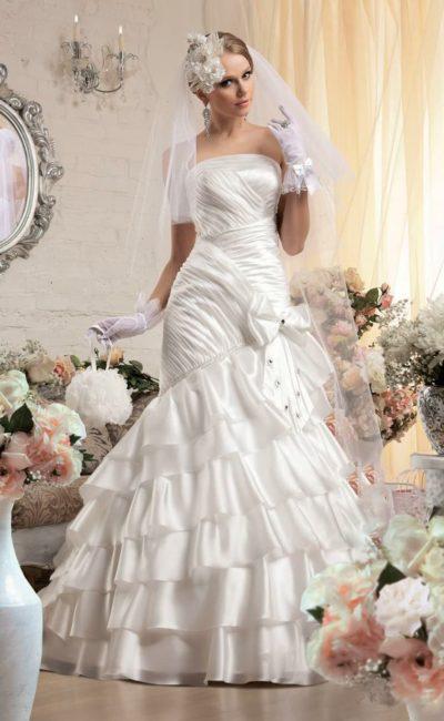Глянцевое свадебное платье силуэта «рыбка», покрытое оборками и драпировками.