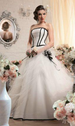 Пышное свадебное платье с полосами бисерной вышивки на корсете и оборками по юбке.