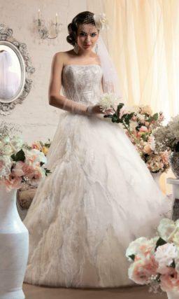 Пышное свадебное платье с глянцевой вышивкой и причудливым узором оборок на юбке.