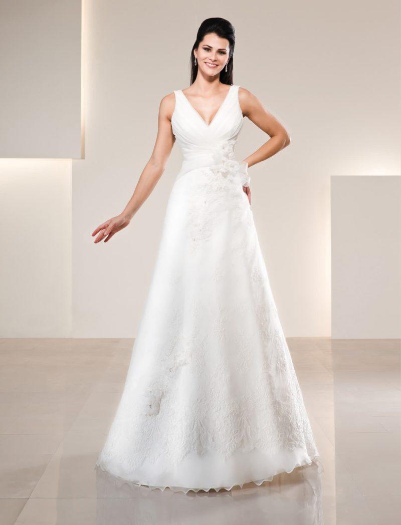 Прямое свадебное платье с V-образным лифом и нежной объемной отделкой сбоку на талии.