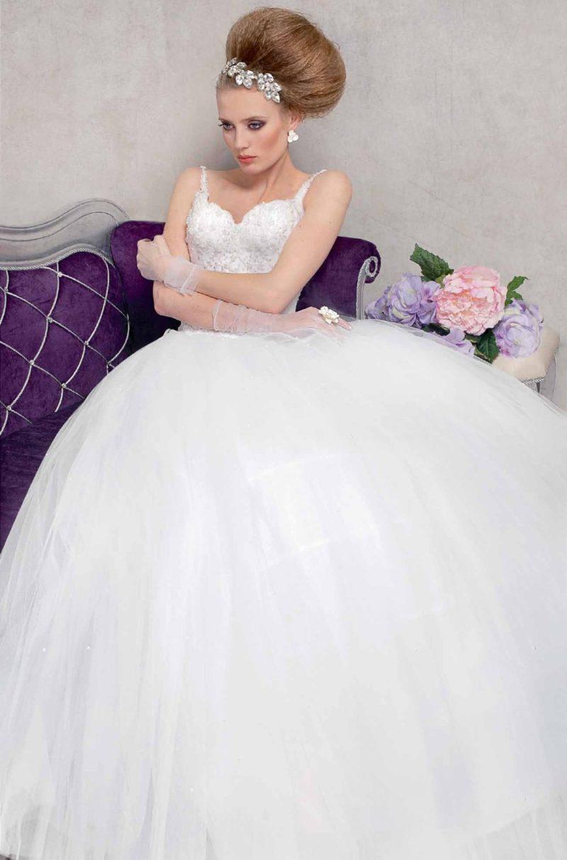 Пышное свадебное платье с фактурным декором корсета, дополненного узкими бретелями.