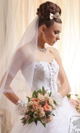 Пышное свадебное платье с объемными бантами на корсете и аппликациями на юбке.