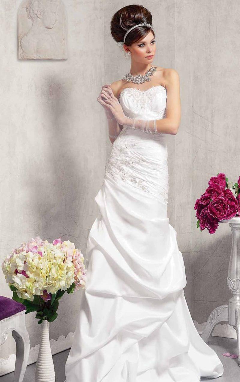 Прямое свадебное платье, драматично декорированное объемными драпировками.