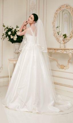 Атласное свадебное платье пышного силуэта с широким поясом, украшенным бантом.