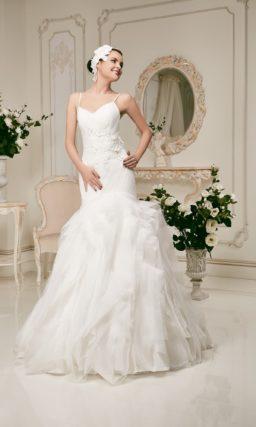 Изящное свадебное платье «рыбка» с тонкими бретельками и пышной отделкой подола.