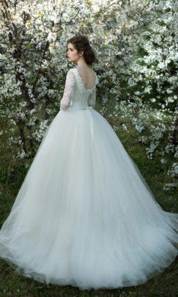 Нежное свадебное платье пышного силуэта с длинными кружевными рукавами и круглым вырезом.