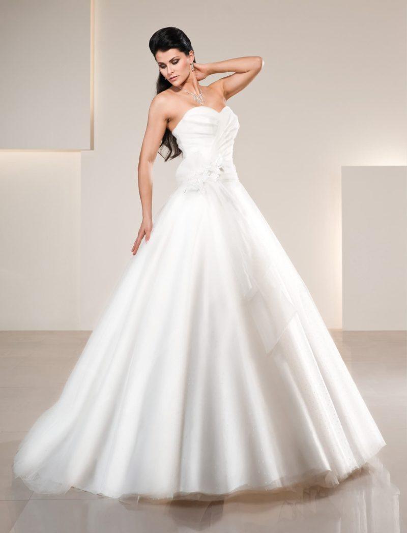 Глянцевое свадебное платье с романтичными драпировками на корсете и юбке А-силуэта.