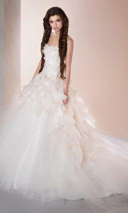 Свадебное платье с открытым лифом и потрясающей пышной юбкой, покрытой оборками.