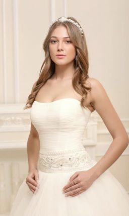 Пышное свадебное платье с открытым лифом и широким роскошным поясом.