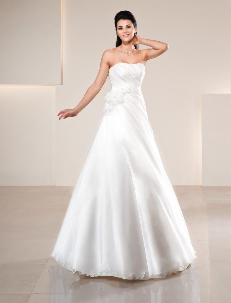 Глянцевое свадебное платье А-силуэта с драпировками и пышными бутонами на талии.