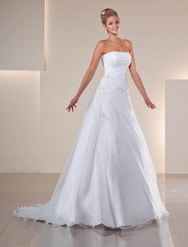 Открытое свадебное платье А-силуэта со сдержанным прямым лифом и полупрозрачным шлейфом.