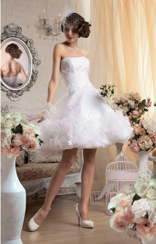 Короткое свадебное платье с полупрозрачными оборками по пышной юбке.