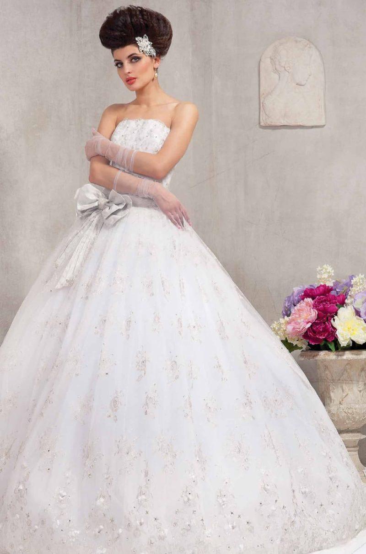 Пышное свадебное платье с фактурным декором юбки и широким атласным поясом с крупным бантом.