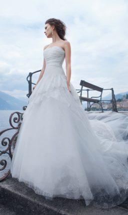 Свадебное платье с юбкой А-силуэта из нескольких слоев ткани разной длины и открытым лифом.
