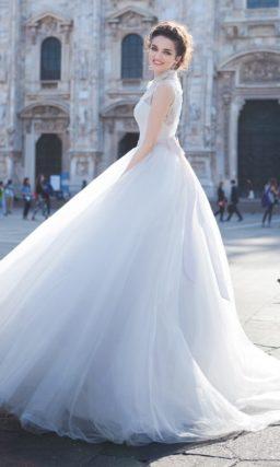 Пышное свадебное платье с закрытым кружевным верхом и тонким пояском на талии.