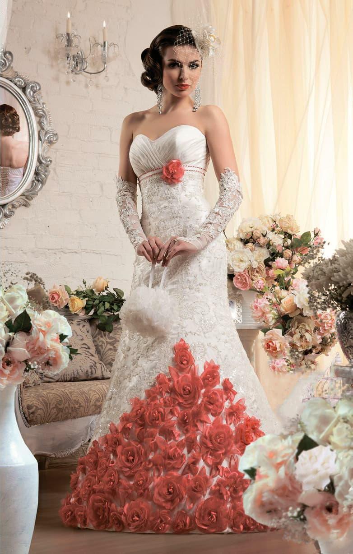 Свадебное платье силуэта «рыбка» с ярким декором на юбке в виде красных бутонов.