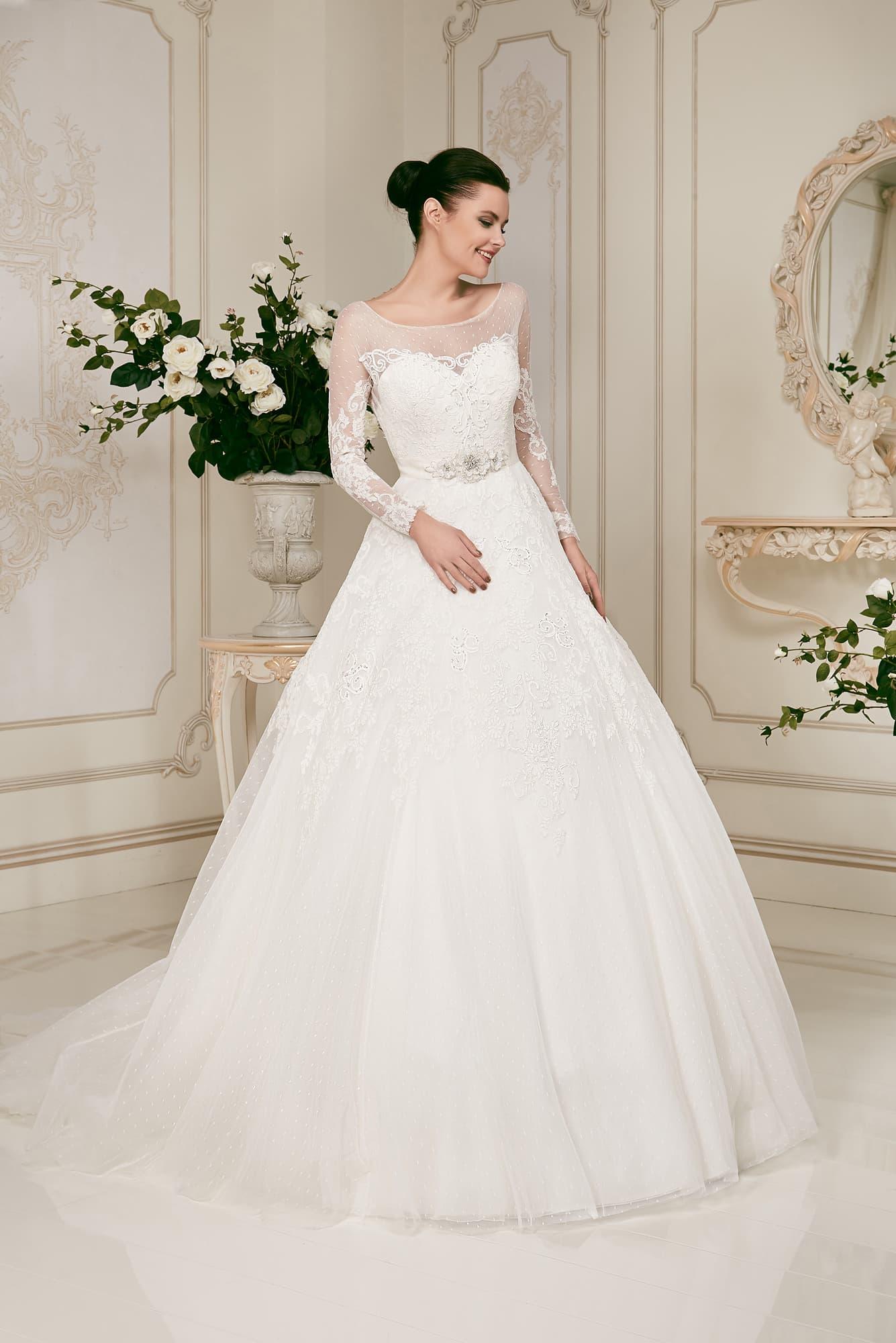5fe35d45f8d Пышное свадебное платье с длинными полупрозрачными рукавами и кружевным  декором.