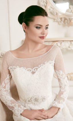 Пышное свадебное платье с длинными полупрозрачными рукавами и кружевным декором.