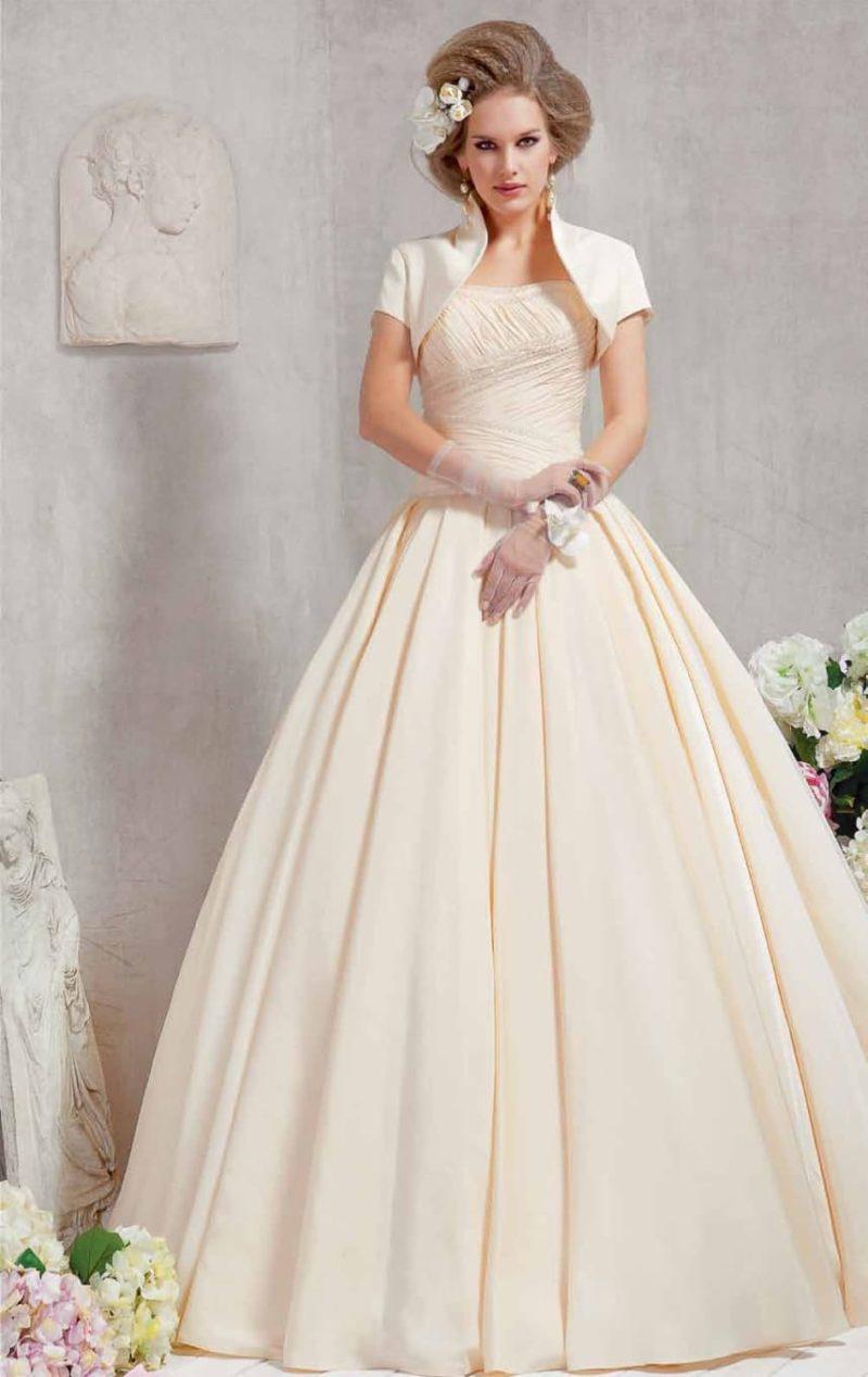 Роскошное свадебное платье цвета слоновой кости с пышным силуэтом и коротким болеро.