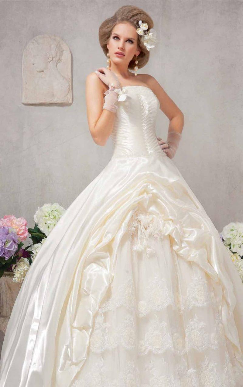 Торжественное свадебное платье с драпировками атласной ткани по юбке.