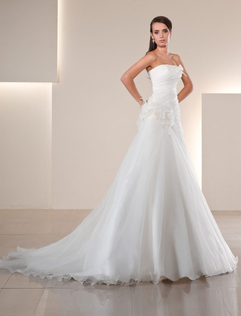 Свадебное платье А-силуэта с длинным шлейфом из нескольких слоев ткани и объемной отделкой.