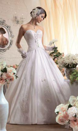 Открытое свадебное платье пышного силуэта с декоративными бантами на корсете.
