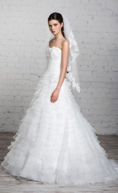 Нежное свадебное платье с объемным декором корсета и горизонтальными оборками по подолу.
