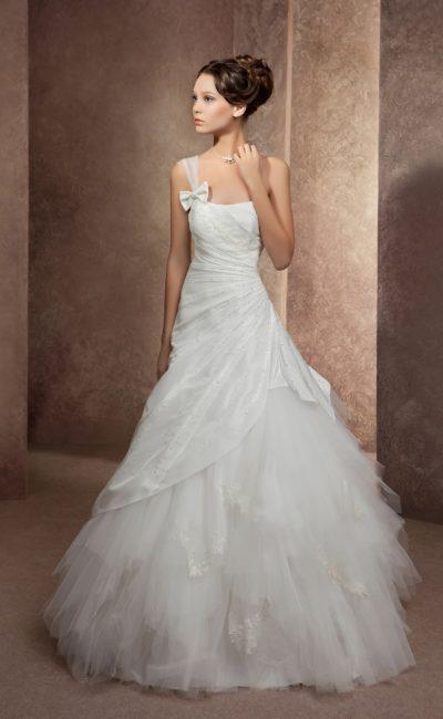 Свадебное платье силуэта «принцесса» с прозрачной бретелью на одном плече и оборками по юбке.