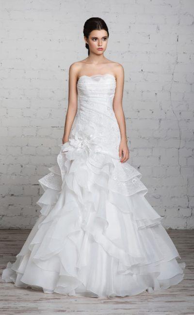 Стильное свадебное платье силуэта «рыбка» со шлейфом и глянцевыми оборками на юбке.