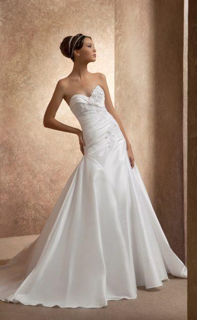 Атласное свадебное платье силуэта «принцесса» с заниженной талией и кружевным декором.