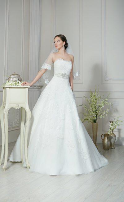 Нежное свадебное платье А-силуэта с кружевным лифом прямого кроя и широким поясом на талии.