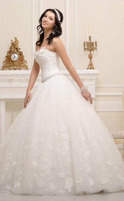 Пышное свадебное платье с открытым лифом, украшенным объемными аппликациями.