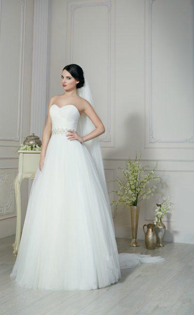 Лаконичное свадебное платье пышного силуэта с декором из драпировок и бисерным поясом.