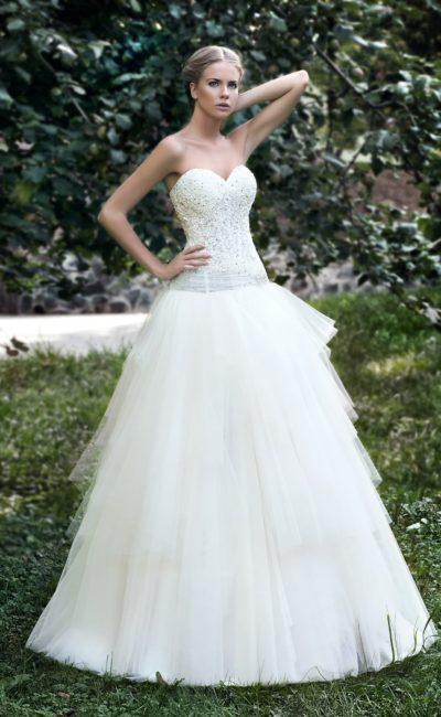 Пышное свадебное платье с многоярусной юбкой из полупрозрачной ткани и вышивкой на корсете.