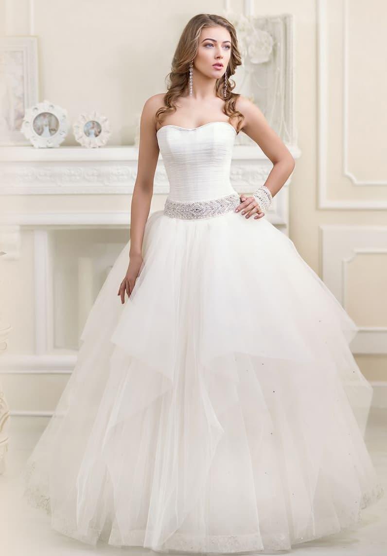 Пышное свадебное платье с открытым корсетом и широким поясом, покрытым вышивкой.