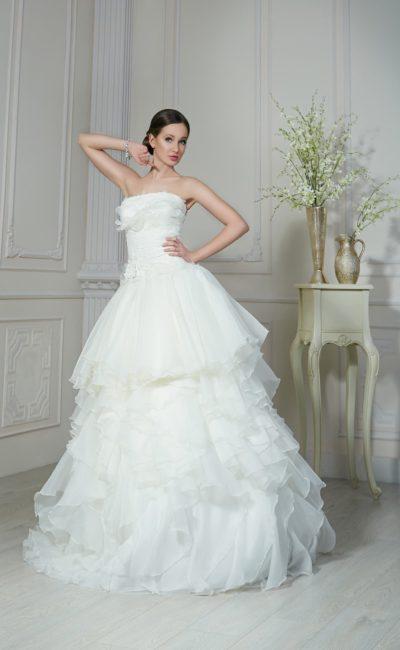 Пышное свадебное платье с прямым кроем лифа и кокетливым декором из оборок на юбке.