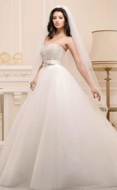 Стильное свадебное платье силуэта «принцесса», расшитое крупными стразами и дополненное поясом.
