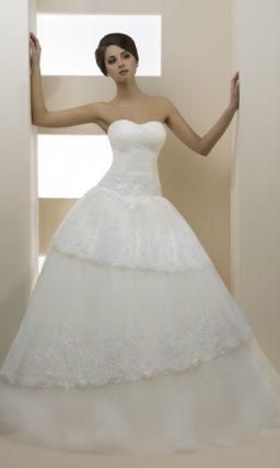 Открытое свадебное платье с пышной многоярусной юбкой, украшенной кружевом.