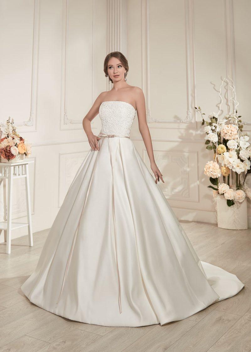 Атласное свадебное платье пышного силуэта с деликатным поясом и кружевным декором верха.