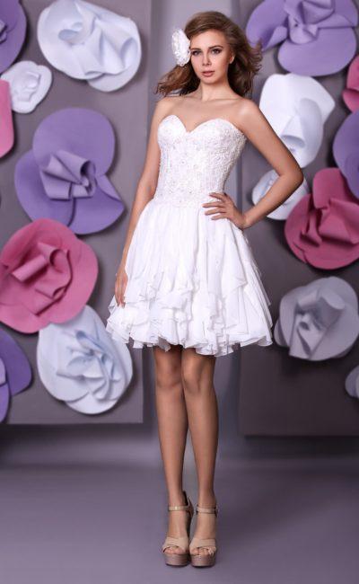 Короткое свадебное платье с открытым корсетом и асимметричными оборками по низу подола.
