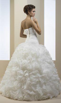 Свадебное платье с заниженной линией талии и юбкой пышного силуэта, покрытой складками ткани.