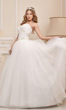 Открытое свадебное платье с многослойной юбкой и сверкающей вышивкой на лифе.