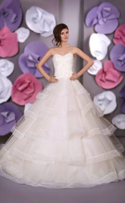 Открытое свадебное платье пышного силуэта с объемными оборками по подолу.