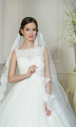 Пышное свадебное платье с вырезом лодочкой и кружевной отделкой нижнего края подола.