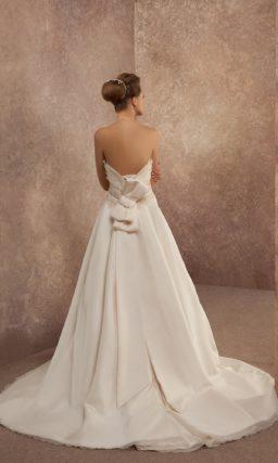 Атласное свадебное платье А-силуэта с роскошным шлейфом сзади и пышным бантом на спинке.