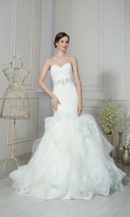 Свадебное платье силуэта «рыбка» с поясом с бантом и романтичной отделкой из оборок на юбке.