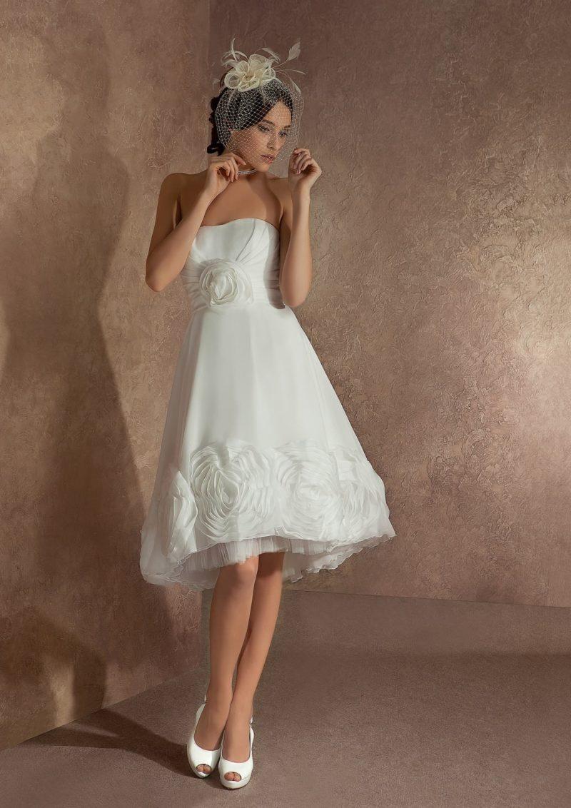 Короткое свадебное платье с открытым лифом и декором из округлых бутонов по юбке.