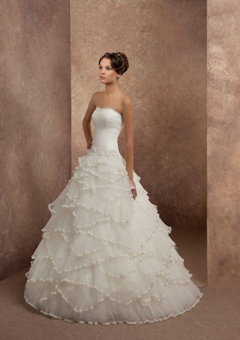 Свадебное платье со шлейфом, покрытой полупрозрачными волнами ткани.