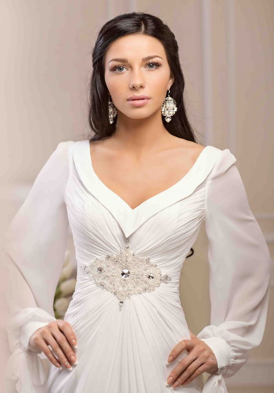Оригинальное прямое свадебное платье с длинными полупрозрачными рукавами.